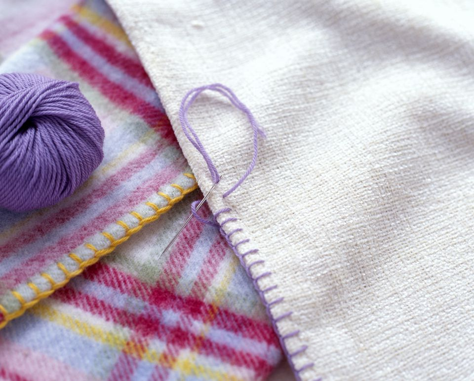 Blanket stitches decorating the edge of a fabric, ball of purple wool nearby