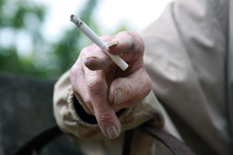 An elderly man holds a cigarette