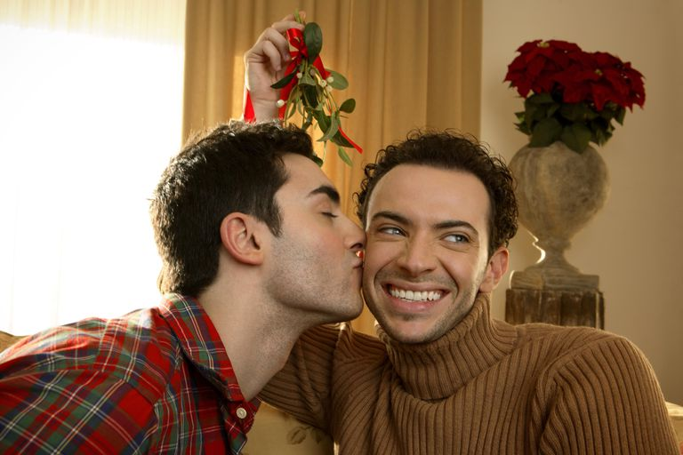 Two young men under mistletoe kissing, close-up