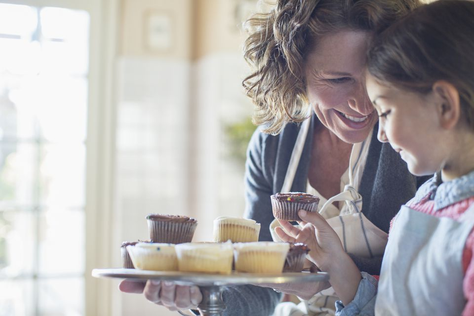 Grandmother offering granddaughter cupcakes