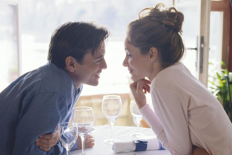 Young couple looking into each other's eyes across table in cafe