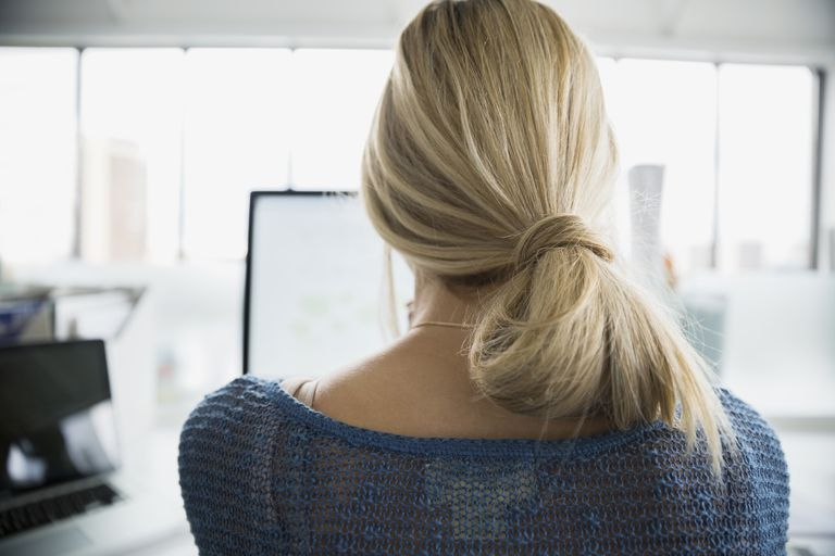 Rear view of blonde businesswoman working at computer