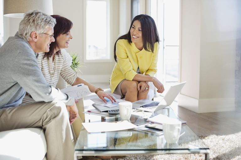 Female financial advisor working with couple in home