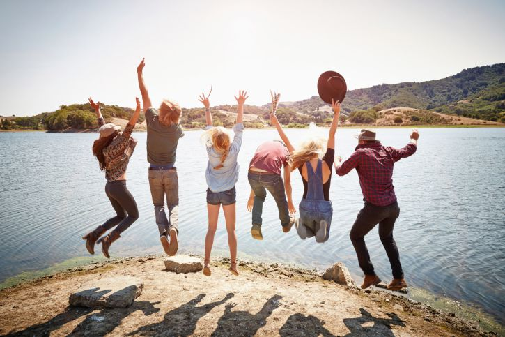 A group of young people jumping off a cliff together.