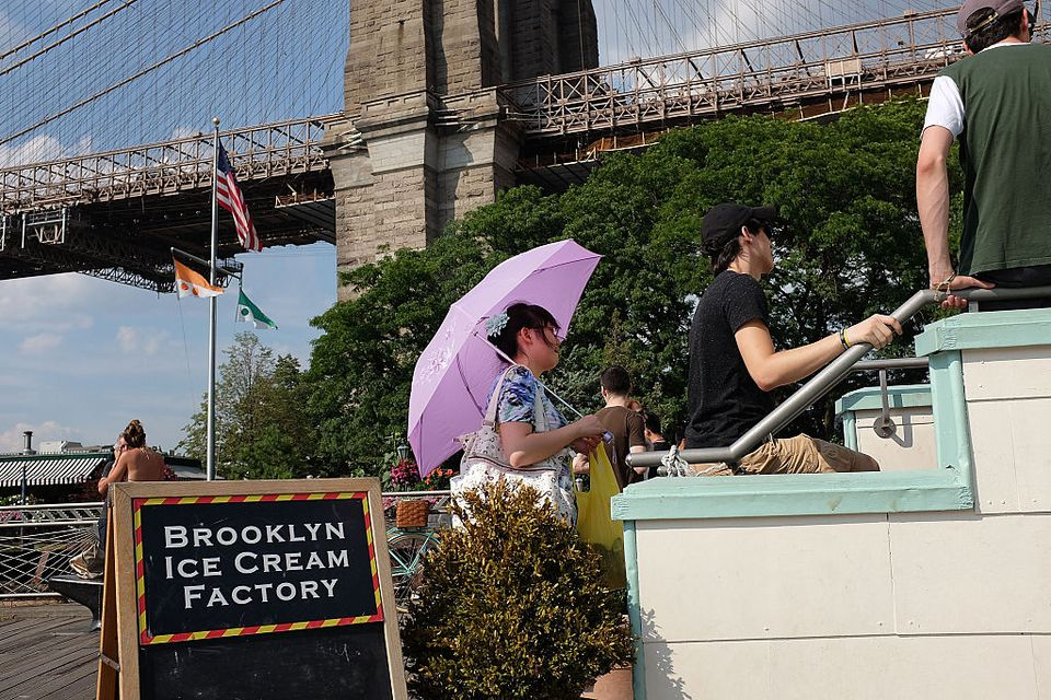 A woman sits in a line for ice cream along the East River in Brooklyn on a sweltering hot afternoon on July 28, 2015 in New York City. With temperatures in the 90's and the heat index feeling over 100 degrees, New Yorkers of all ages have been flocking to pools, beaches and air conditioned rooms to try and stay cool. More hot and humid days are forecast for the remainder of the week