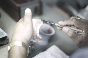 a dentist works on a set of dentures