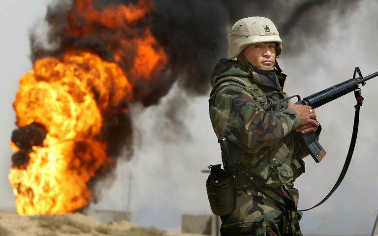 US soldier standing guard as Iraqi oil well burns.