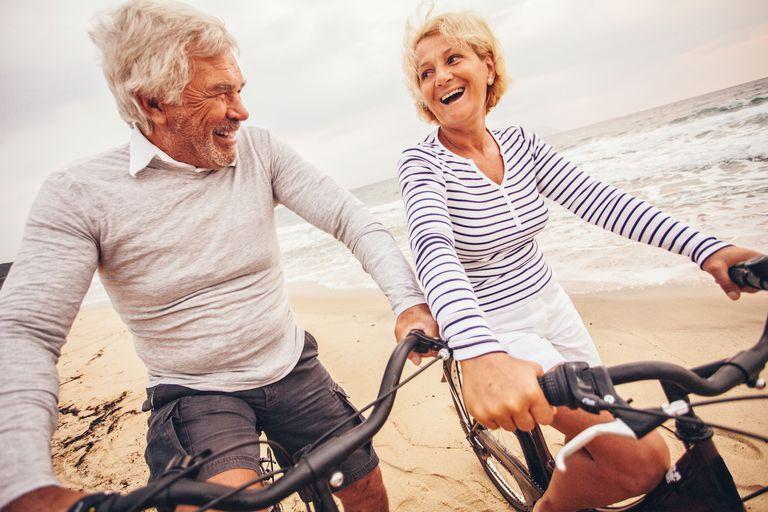 Active senior couple riding bikes on beach