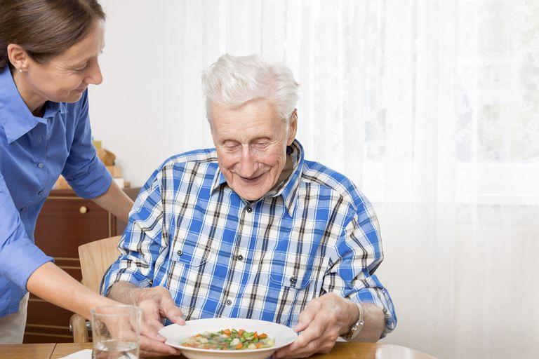 woman helping elderly man eat