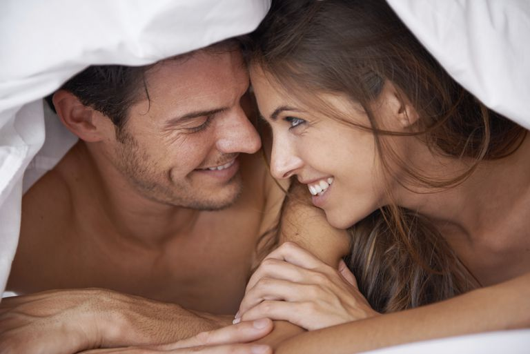 Couple under blanket considering whether to have sex after ovulation