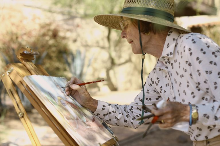 older woman at an easel painting