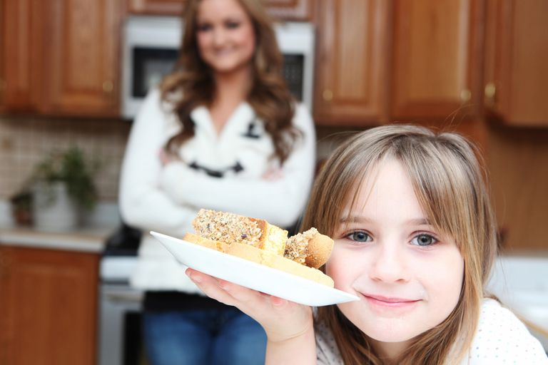 Little girl in kitchen is showing off a homemade plate of biscotti. Mother defocused in the background