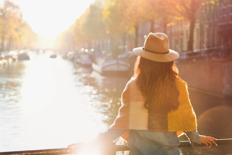 Woman looking at sunny autumn canal view, Amsterdam