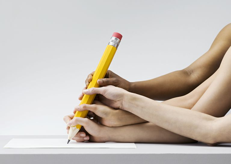 Many hands on a huge pencil