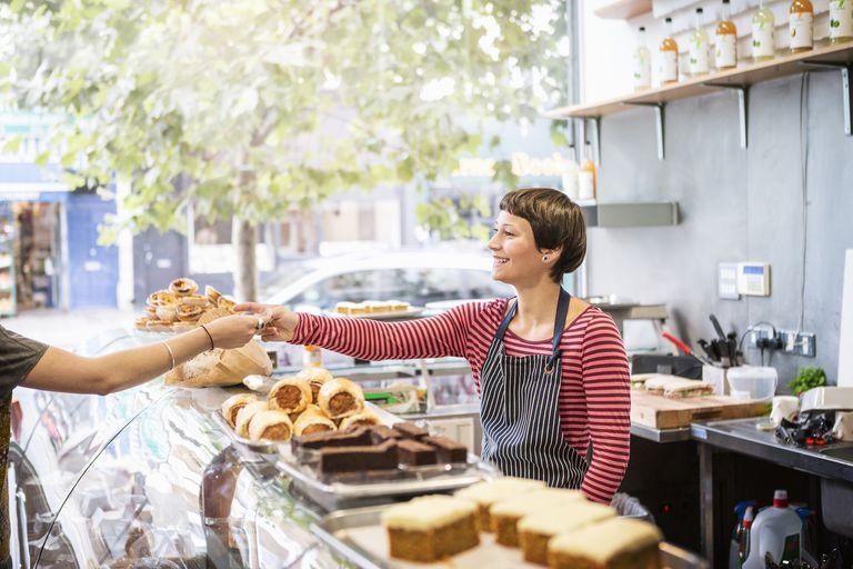 shopkeeper serving customer in delicatessen shop