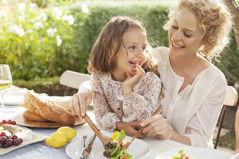 Mother and daughter eating in garden