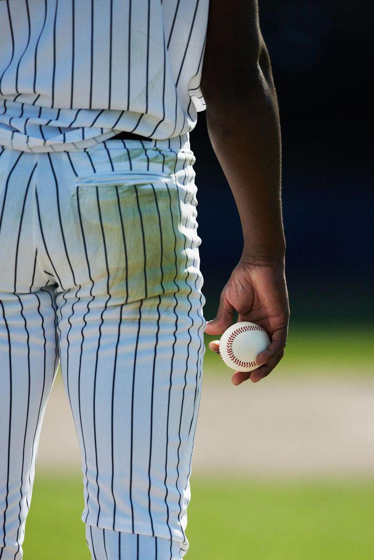 Professional baseball pitcher holding baseball, rear view, preparing to pitch