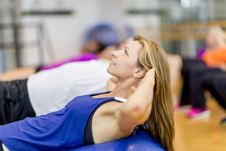 Woman Doing Sit Ups in Fitness Class