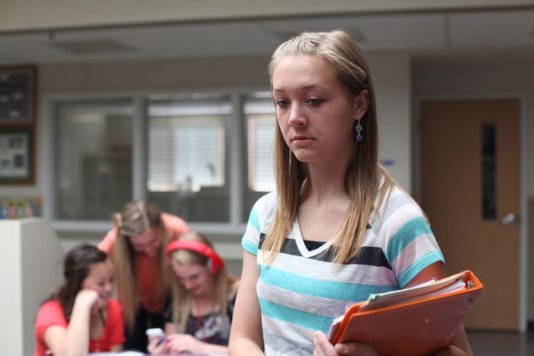 upset teen girl with other girls in the background