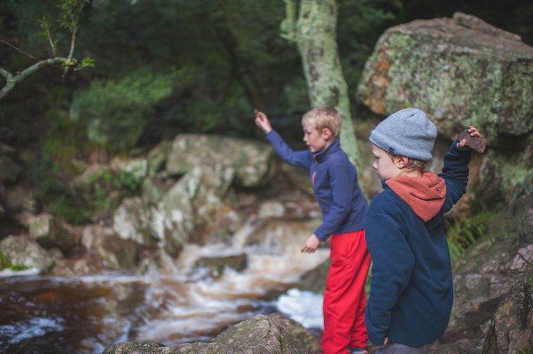 Two Young Boys throwing stones in a stream
