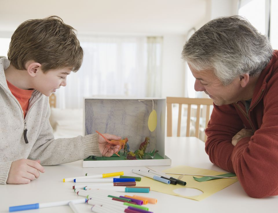 Father and son working on dinosaur project
