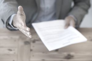 Man holding out hand with resume in the other hand