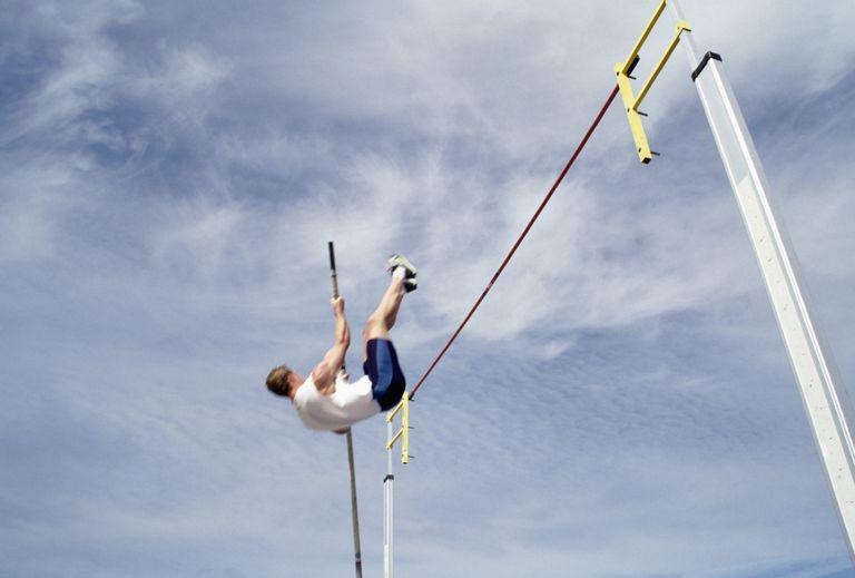A male pole vault athlete hoists himself through the air to clear the bar.