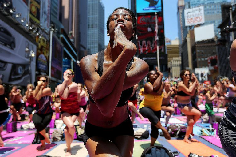 People practicing yoga in Times Square, New York, demonstrate the concept of cultural diffusion.
