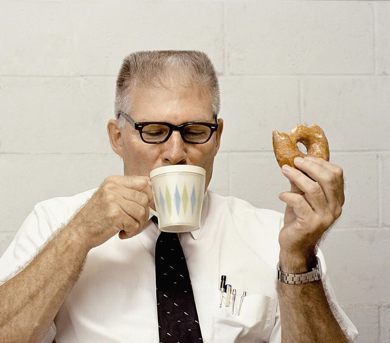 Man on a coffee break with donut
