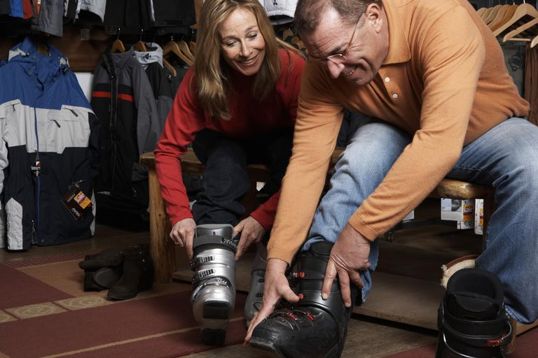 Mature Man and woman trying on skl boots in sports shop