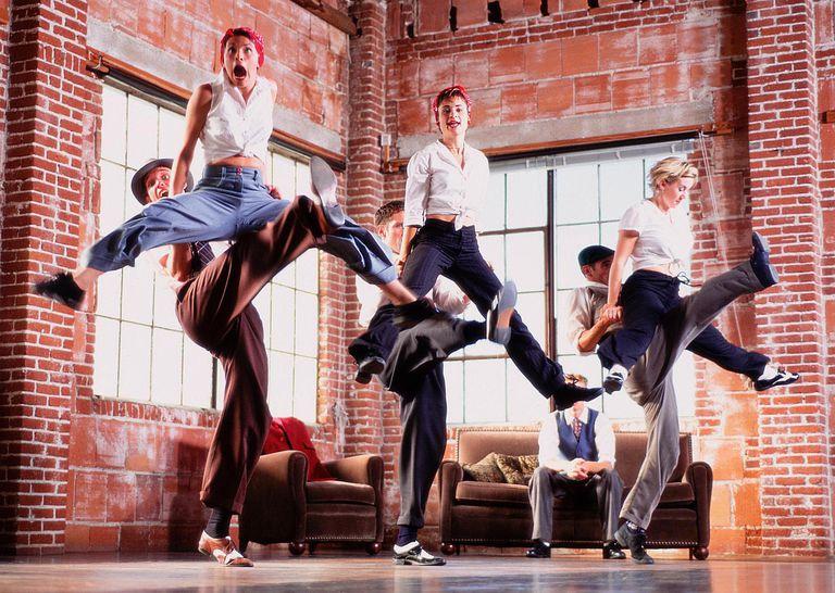 Couples swing dancing, men lifting women