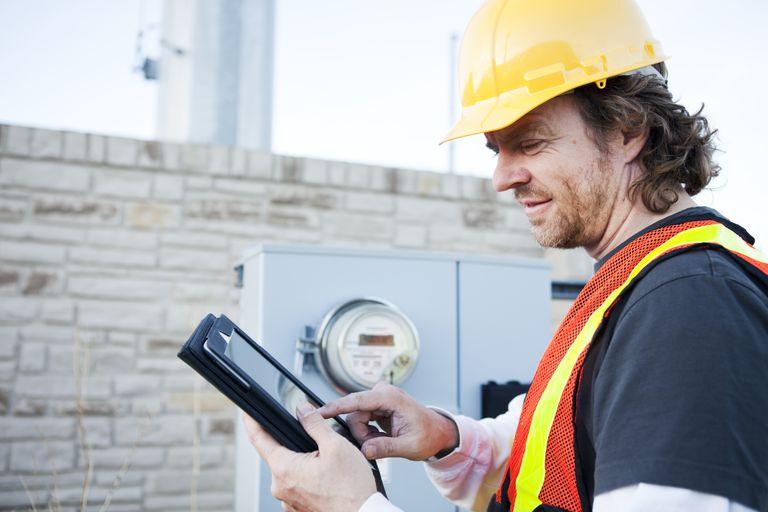 Power Line Technician Using Tablet Computer