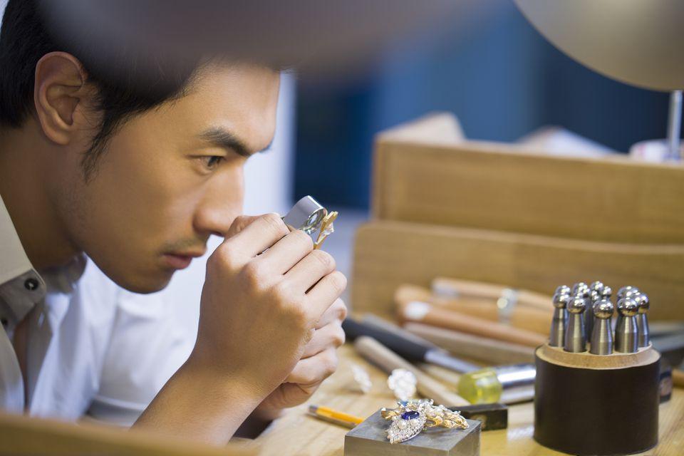 A jeweler examining a diamond with loupe