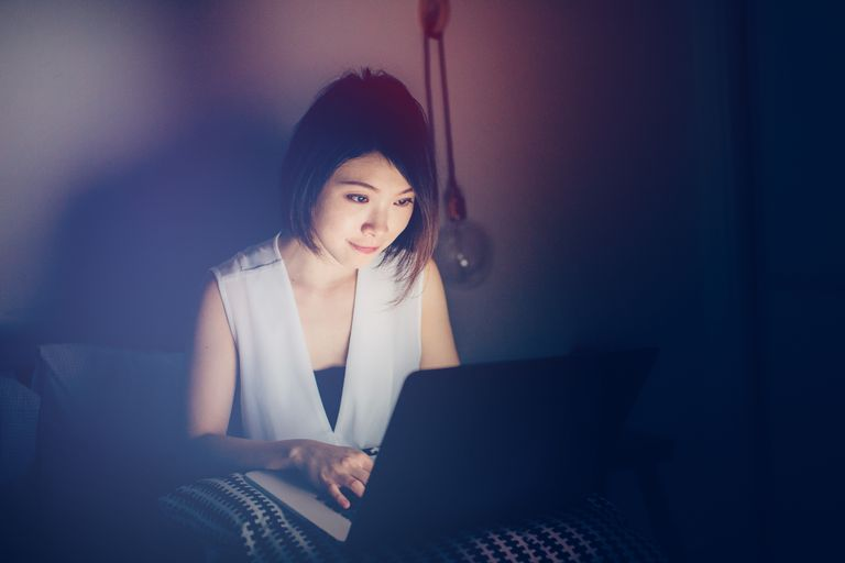 Young woman using laptop on bed