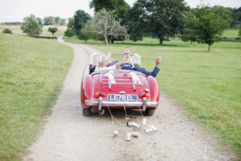 Bride and groom waving in convertible car