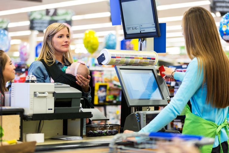 Cashier swiping loyalty card for mother in grocery store