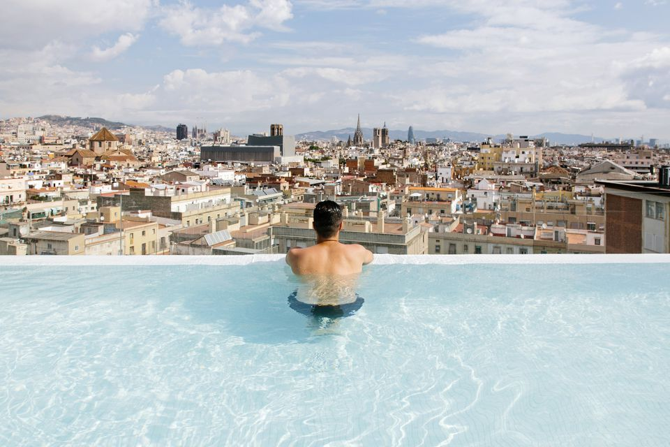A man at a hotel pool against the skyline of Barcelona.