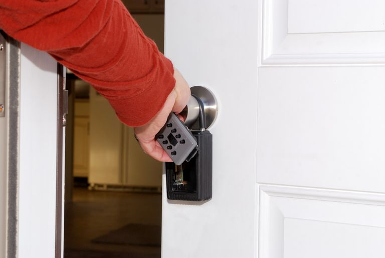 man opening door to house with key lockbox on handle