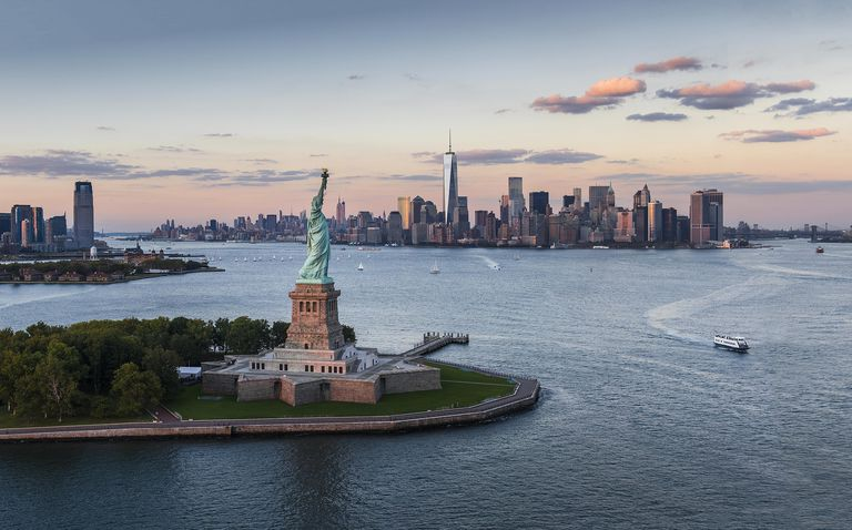 USA, New York State, New York City, Aerial view of city with Statue of Liberty at sunset