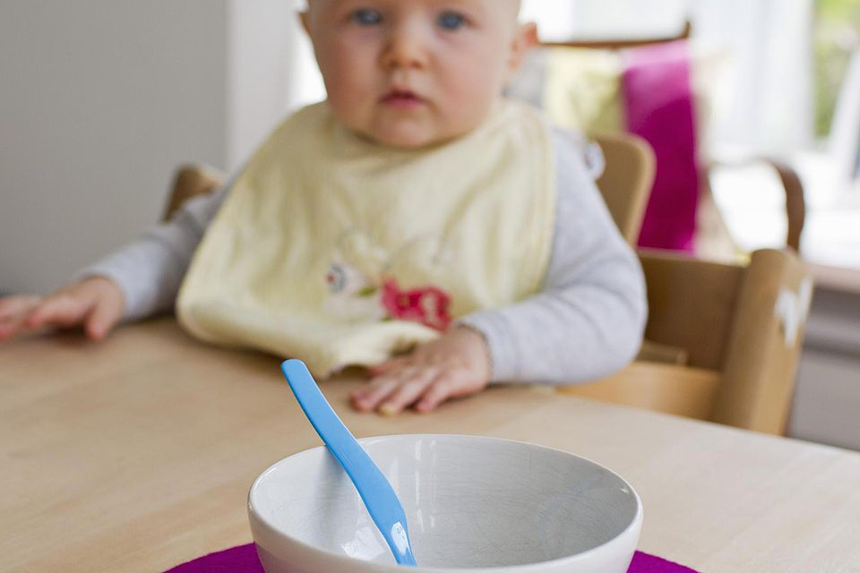 Baby girl staring at empty bowl and spoon