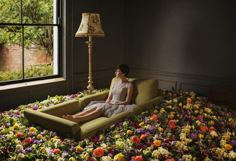 Woman sitting on sofa surrounded by flowers
