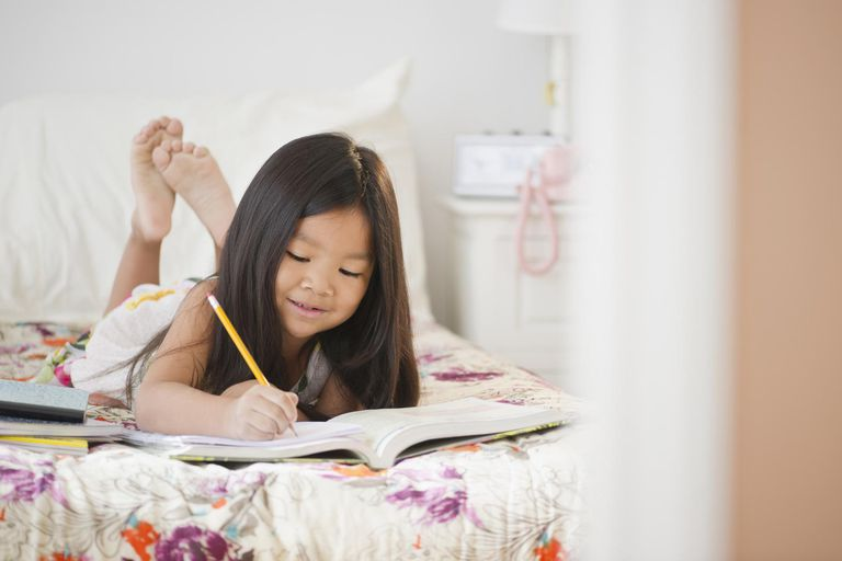 Korean girl doing homework on bed