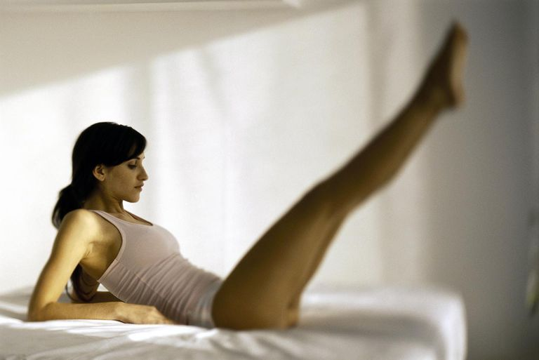 Woman doing strengthening exercises on bed