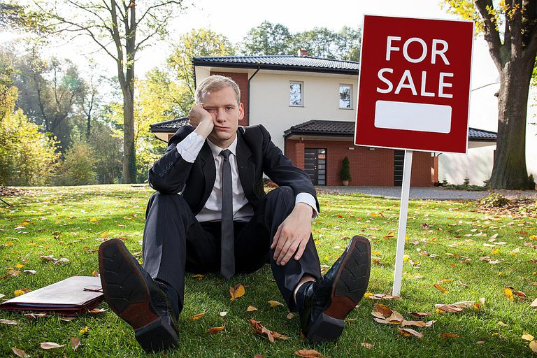 real estate agent sitting on the grass looking depressed