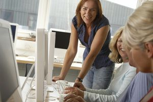 Woman teaching mature and senior women at desk with computers, smiling