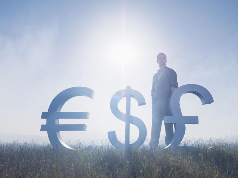 Sun shining over businessman and euro, dollar and British pound symbols in field