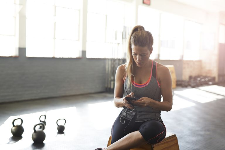 Woman checking smartphone at the gym