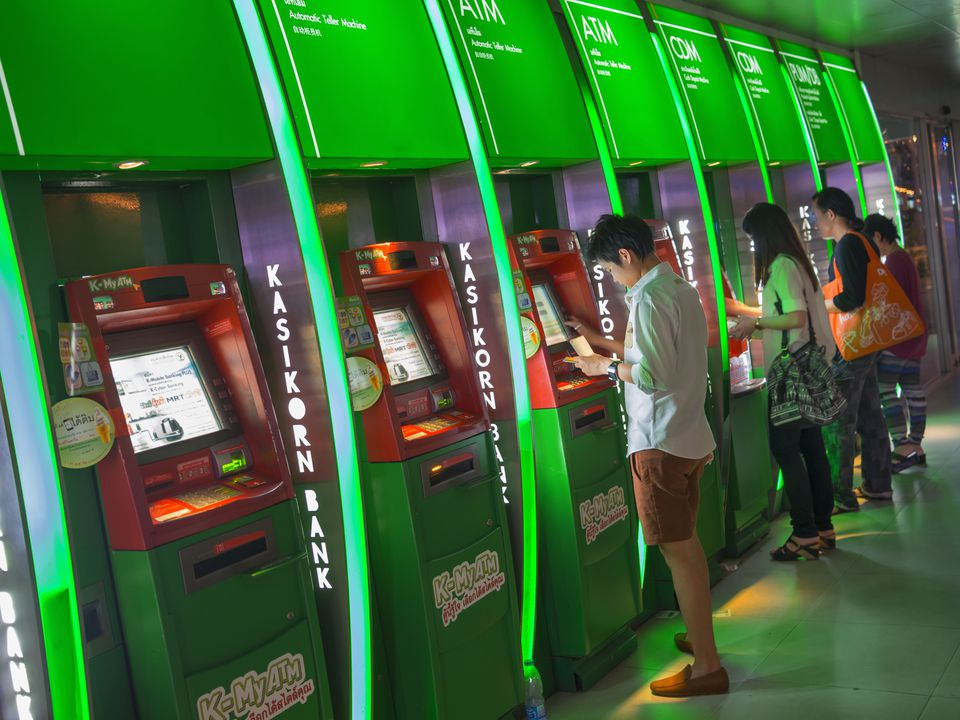 People using a row of green ATMs in Thailand