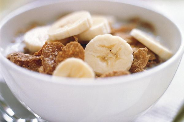 Bowl of corn flakes with slices of banana on newspaper