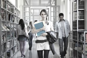 college girl with books walking down library hallway